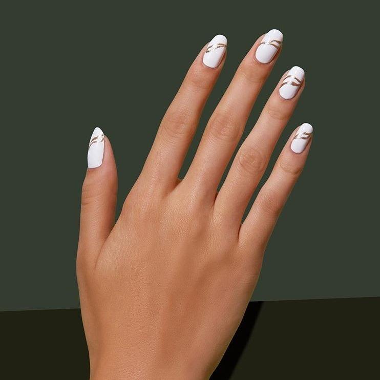 طراحی ناخن که ترکیب نوارهای نازک طلایی روی لاک سفید است