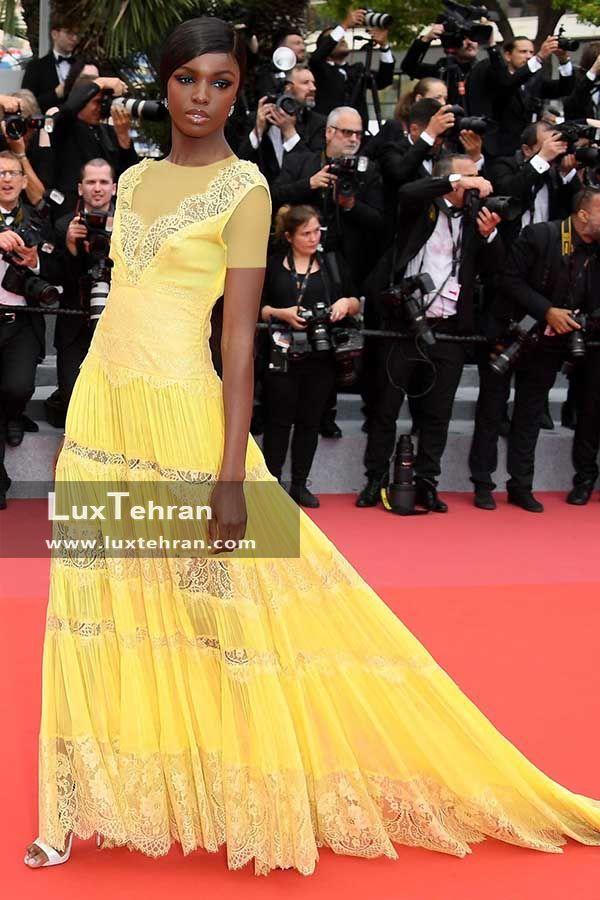 LEOMIE ANDERSON است که با لباس بلند زرد دنباله دار در اکران فیلم YOMEDDINE در جشنواره کن 2018