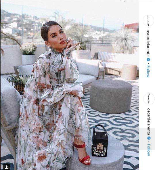 لباس رنگارنگ گل دار مجللی از برند اسکار دلارنتا را در کنار کیف لاکچری Alibi