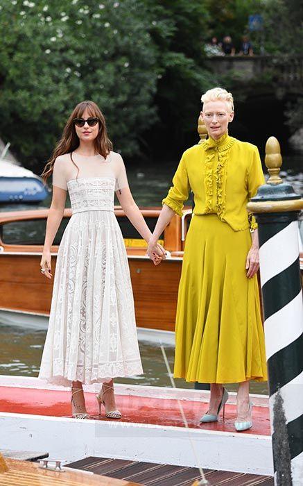 TILDA SWINTON را که در لباس بلند زرد رنگ در کنار داکوتا جانسون