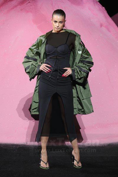 تیلور در این عکس، لباس مشکی  رنگ  خود را از برند FENTY  PUMA با کت بارانی