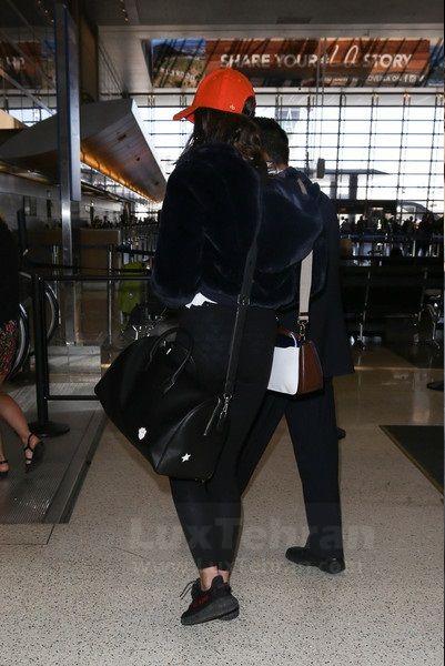 تیلور با کیف  دافل  در فرودگاه  لس  آنجلس  و کلاه قرمز