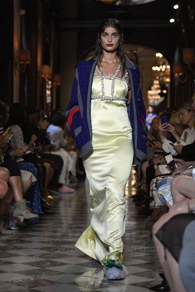 تیلور هیل  در این عکس، دکلته لیمویی رنگ بلند بدون آستین از برند MIU MIU